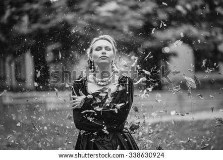 Beautiful blonde girl in medieval dress is black inside the vortex of autumn leaves, tranquility, peace, happiness - stock photo