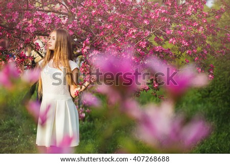Beautiful blonde girl in pink peach and sakura garden. Beautiful female outdoors spring portrait, young woman with flowers at green blossom park  concept - stock photo