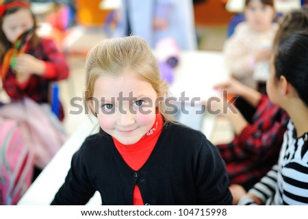 Beautiful blonde girl in school with her classmates - stock photo