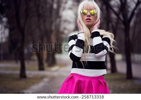 Beautiful blonde girl in sunglasses outdoors - stock photo