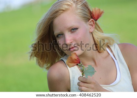 Beautiful  blonde girl in the garden on a sunny day - stock photo
