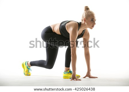 Beautiful blonde girl in the sportswear does split squats on the white background in the studio. She wears yellow-cyan sneakers, mint socks, black pants and black top. She presses her torso to the - stock photo