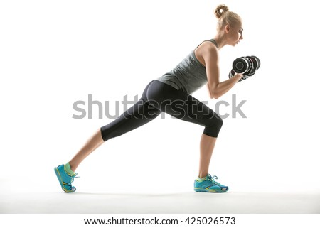 Beautiful blonde girl in the sportswear with dumbbells in her hands does split squats on the white background in the studio. She wears cyan-yellow sneakers, mint socks, black pants and gray sleeveless