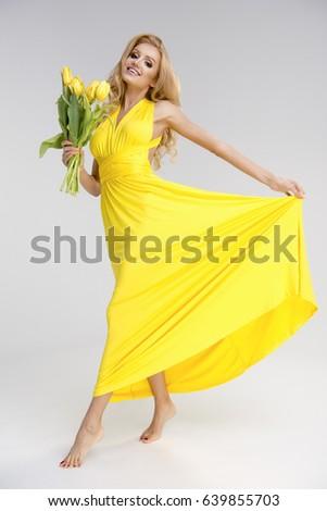 Beautiful blonde girl yellow dress flowers stock photo royalty free beautiful blonde girl in yellow dress with flowers in hands mightylinksfo