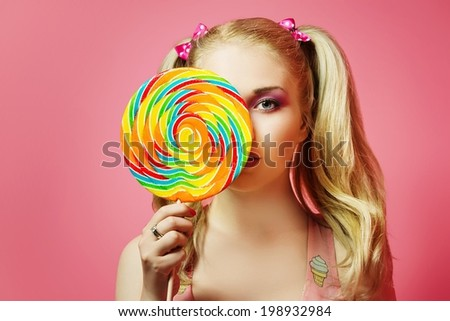 Beautiful blonde girl is looks for candie, on a pink background - stock photo