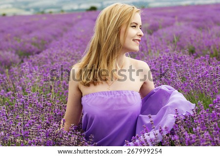 Beautiful blonde girl is wearing purple silk dress in fairy field of lavender. Summer time - stock photo