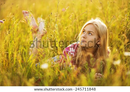 Beautiful blonde girl lying in the tall grass - stock photo