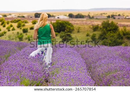 beautiful blonde girl on lavender field in summer - stock photo