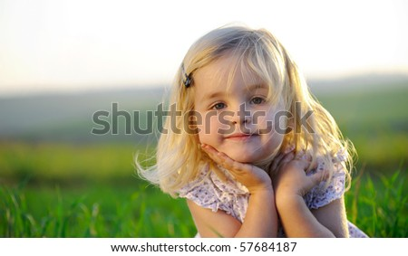 Beautiful blonde girl outside in a field with sunlight on her hair. - stock photo