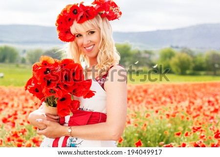 Beautiful blonde girl resting on the poppy field