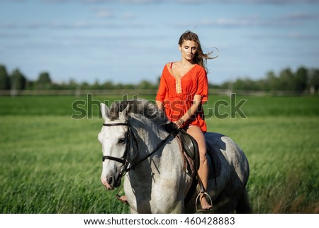 Beautiful blonde girl riding a horse in countryside