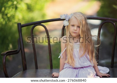 Beautiful blonde girl sitting on a vintage wooden bench in summer garden with flowers - stock photo