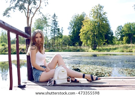 beautiful blonde girl sitting on the dock