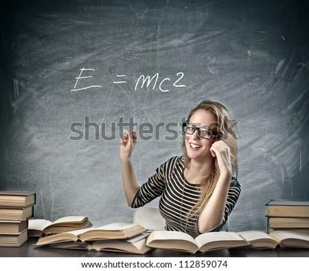 Beautiful blonde girl teaching physics - stock photo