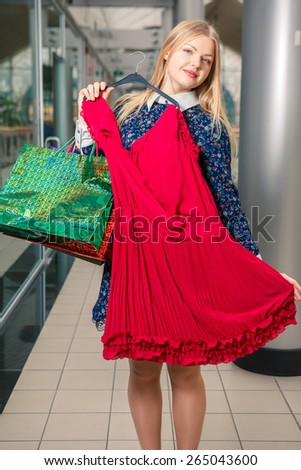 Beautiful  blonde girl trying dress on the mall background. shopping, sale, happy people and tourism concept - stock photo