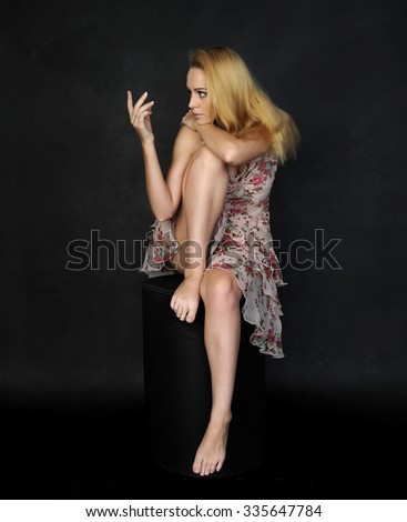 beautiful blonde girl wearing a flower print summer dress, seated in glamorous pinup pose, hand reaching out to touch. isolated on black.  - stock photo
