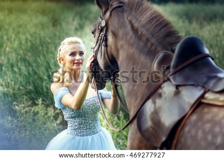 Beautiful blonde girl wears long blue dress looking at brown horse in the park.