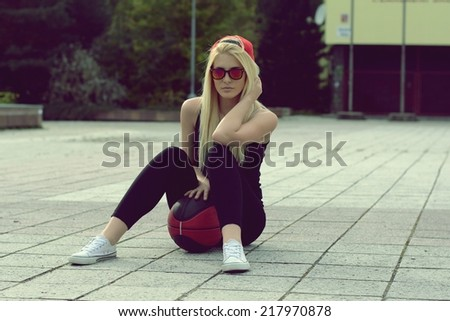 Beautiful blonde girl with a basketball ball - stock photo