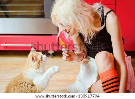 Beautiful blonde girl with candy in hand and cat sitting on a kitchen floor - stock photo
