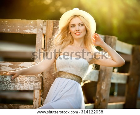 Beautiful blonde girl with country look near an old wooden fence in sunny summer day. Attractive woman with white hat and dress, American country style farmer. Long fair hair female in rustic style - stock photo