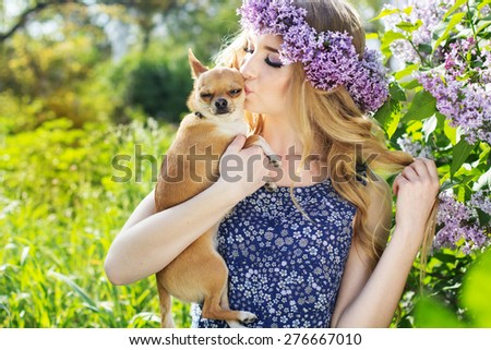 Beautiful blonde girl with long hair with a lilac flowers and small chihuahua dog - stock photo