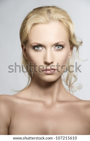 beautiful blonde girl with nudes shoulders and natural makeup, she is in front of the camera and looks in to the lens with serious expression - stock photo