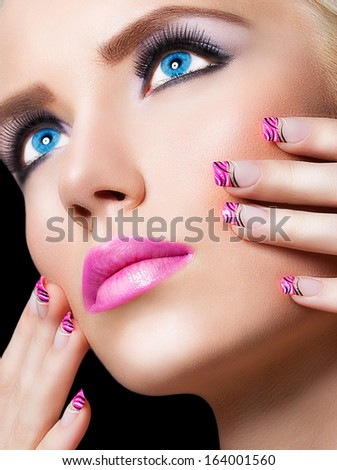 Beautiful blonde girl with pink lips and nails on black background - stock photo