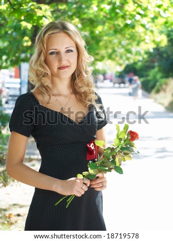 beautiful blonde girl with roses waiting for somebody at street