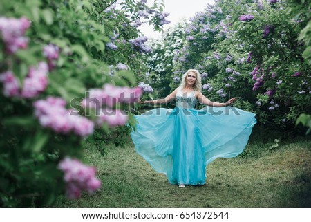 Beautiful blonde girl with wavy hair in a long blue dress with flying train in the summer garden with lilacs.
