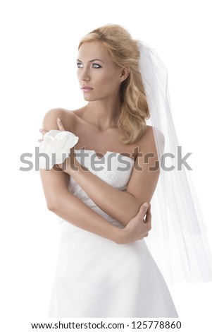 beautiful blonde girl with white wedding dress, she looks at right with the left hand on the right shoulder and the right hand on the left arm