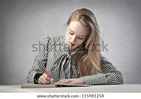 Beautiful blonde girl writing - stock photo