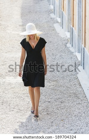Beautiful blonde girl young woman walking in white hat and little black dress - stock photo