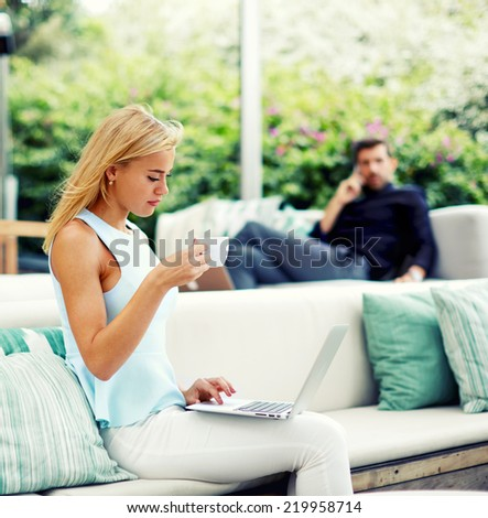 Beautiful blonde hair woman drinking coffee while using computer pc at her work break, handsome rich businessman looking for beautiful woman seated near from him in light modern terrace of lounge bar - stock photo
