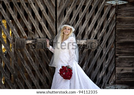Beautiful blonde haired bride in vintage wedding gown in front of unique barn doors with red rose bouquet - stock photo