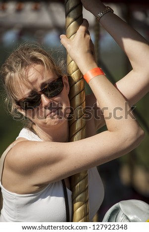 Beautiful, blonde-haired mother tired of riding the carousel at the fair. - stock photo