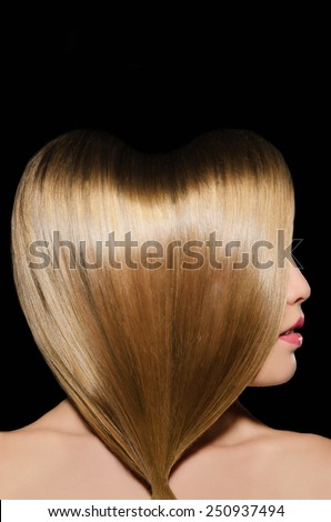 Beautiful blonde hairstyle in shape of heart on dark background - stock photo