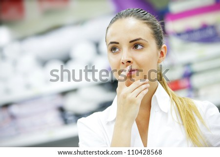 Beautiful blonde, hand to lips, chooses product in supermarket
