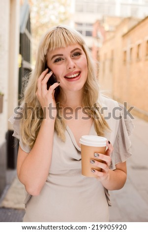 beautiful blonde holding coffee and phone.