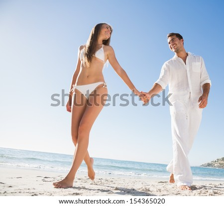 Beautiful blonde holding hands with happy boyfriend on the beach - stock photo