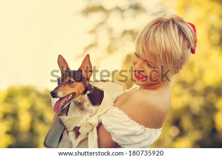 Beautiful blonde hugging her dog. Toned image and selective focus on women face. - stock photo