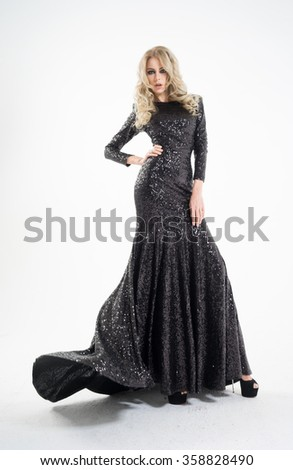 Beautiful blonde in a black dress on a white background, in black shoes - stock photo