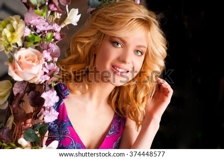 Beautiful blonde in a dress with floral garlands in the studio