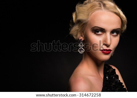Beautiful blonde in a stylish image of a dark background. Elegant accessories and beautiful dress. Romantic and mysterious figure model.