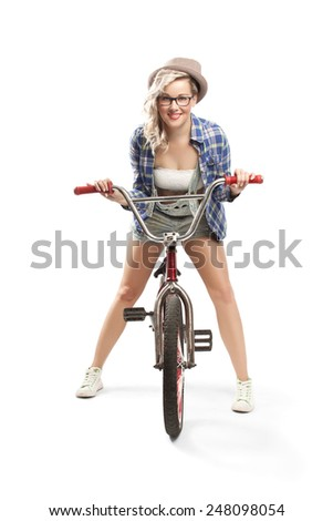 Beautiful blonde in checkered shirt and denim short pants with braces with the bike posing on a white background in a studio. Fashion photography.