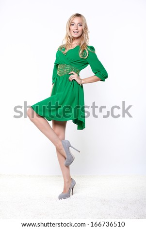 beautiful blonde in green dress has his hand on the waist - stock photo
