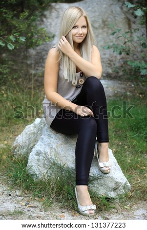 Beautiful blonde in leggings and shirt sitting on a stone in nature, fashion photo