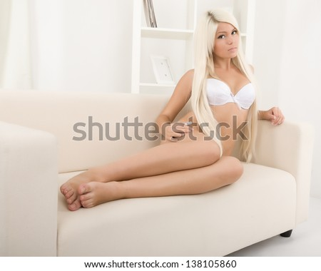 Beautiful blonde in lingerie on the couch - stock photo