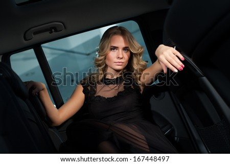 Beautiful blonde in the cabin of an expensive car