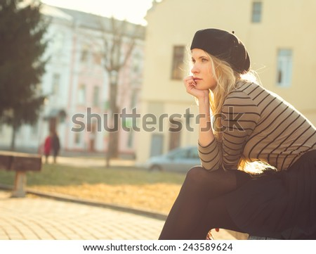 beautiful blonde in the French style sits on a city street on a sunny spring day - stock photo