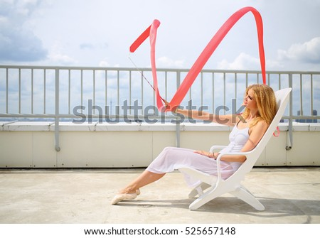 Beautiful blonde in white sitting on a lounger with red curly ribbon on the roof of a multistory building
